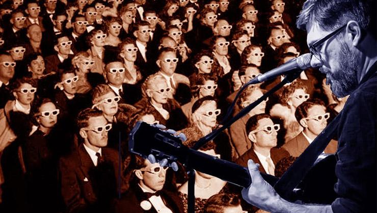 Dekker + Katie Keddie Jamcafe (man performing guitar in front of cinema of people in sunglasses)
